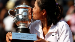 Li Na kisses the winner's trophy after ending the French Open reign of Francesca Schiavone in Paris on Saturday