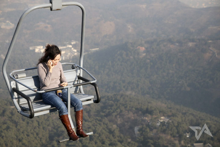 woman on phone chairlift