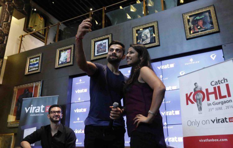 Holding the camera phone - Virat Kohli with a fan at Hard Rock cafe, Gurgaon.